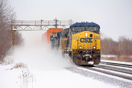 A westbound CSX stack train kicks up a cloud of snow as it passes beneath an old signal bridge in Perry in February 2013. (Photograph by Craig Sanders)