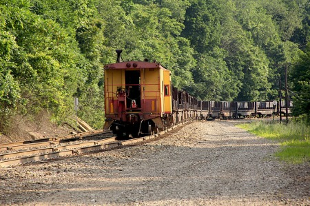 The slab train's caboose and train lean into a curve.