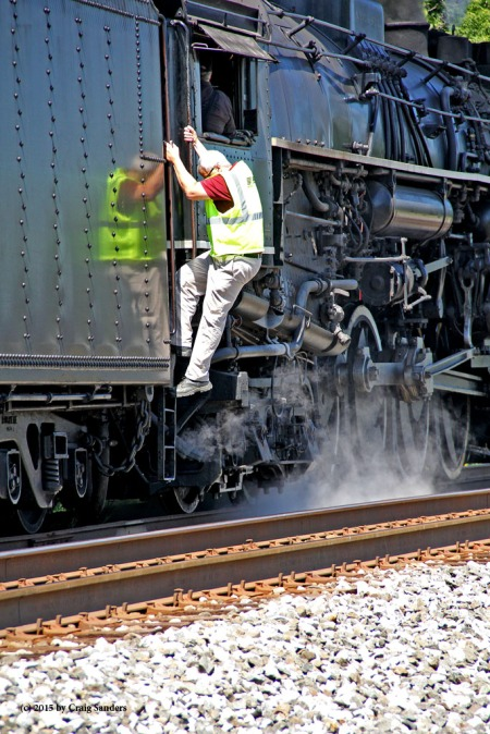 The bright sunlight washed out the color in the safety vest of this Norfolk Southern supervisor, but the reflection on the tender of the 765 captures the colors well.